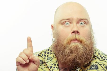 casual man: Surprised bearded man pointing up