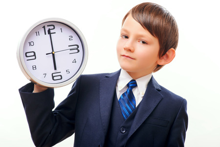career timing: Business child in suit and tie posing with clock Stock Photo