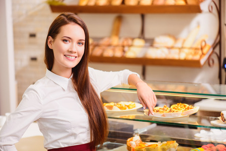 lifestyle caucasian: Beautiful young saleswoman in a bakery Stock Photo