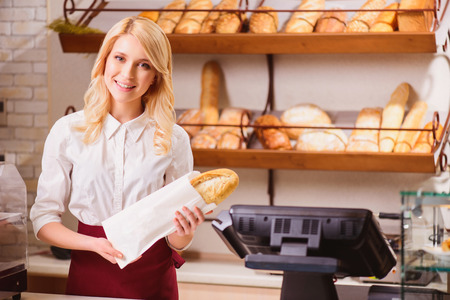 Beautiful young shop assistant in a bakery Banco de Imagens