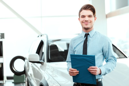 car rent: Perfect car dealer. Portrait of handsome young car sales man in formalwear holding a clipboard and smiling at camera in a car dealership Stock Photo