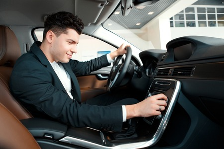 go inside: Let us go for a ride. Handsome young businessman examining the car at the dealership while sitting inside the new car and touching the gear box