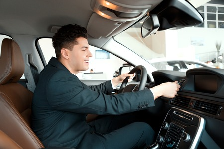 go inside: Let us go for a ride. Handsome young businessman examining the car at the dealership while sitting inside the new car and touching the steering wheel