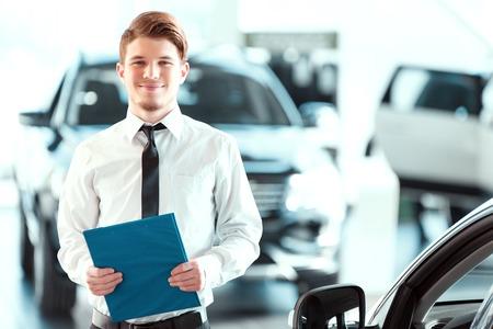 車両検索の助手。クリップボードに保持し、中古車販売店でカメラ目線の正装でハンサムな若い車の販売人の肖像画