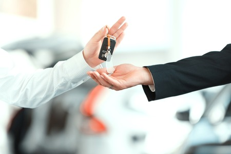 Here is your key. Closeup of man giving key to the car owner while standing in front of a car Stock Photo