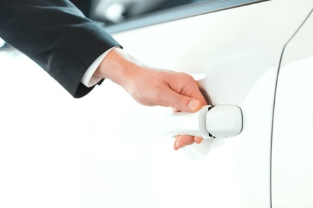 Hand on handle. Closeup of man in formalwear opening a car door in car dealership photo