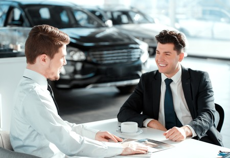 salesman: Salesman and customer. Side view of a handsome sales man in car dealership showing corporate booklets to the client while drinking coffee