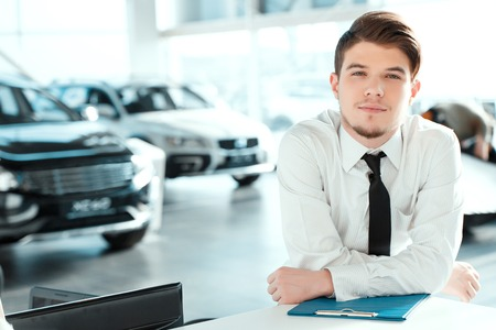 car: Young professional.  Portrait of handsome young sales man in formalwear posing with a note pad in car dealership