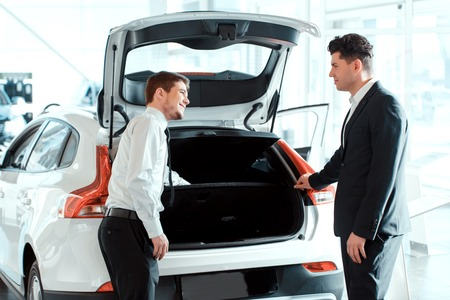 This model is popular. Rear view of a young handsome salesman speaking with his satisfied client in car dealership while standing at new car Stock Photo