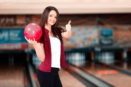 bolos: Mi juego favorito. Hermosas mujeres j�venes la celebraci�n de una bola de boliche mientras que se opone boleras y mostrando su pulgar para arriba Foto de archivo