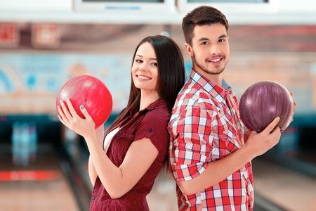 bolos: Hombre joven alegre y mujeres posando de espaldas mientras est� de pie en contra de boleras y bolas celebraci�n Foto de archivo
