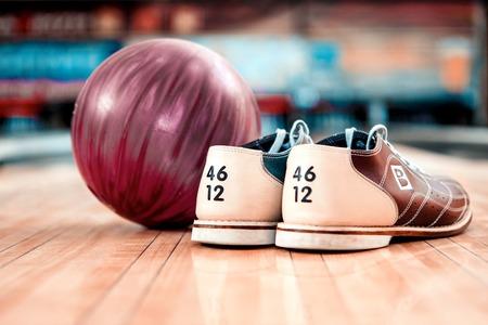 bolos: Primer plano de los zapatos de bowling y bola de color lila que mienten en la bolera