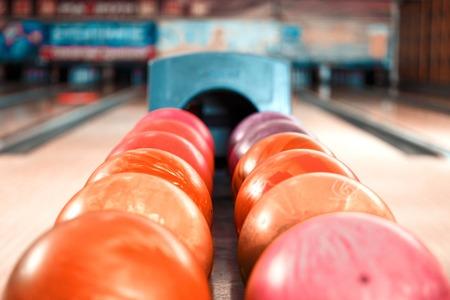 bolos: Close up de brillante bola de bowling roja que miente en las filas de otras bolas de colores