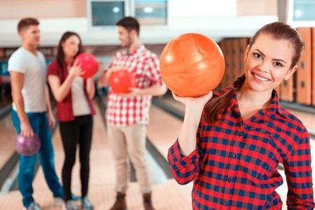 bolos: Jugador hermoso y confiado. Joven y bella mujer una bola de boliche mientras que tres personas comunicarse contra boliches Foto de archivo
