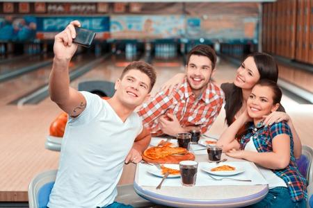 personas reunidas: Fin de semana con amigos. Grupo de gente alegre haciendo Autofoto mientras que comer pizza en el club de bolos Foto de archivo
