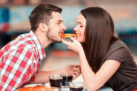 date: Closeup image of young attractive woman and man eating one piece of pizza with bowling alley in the background