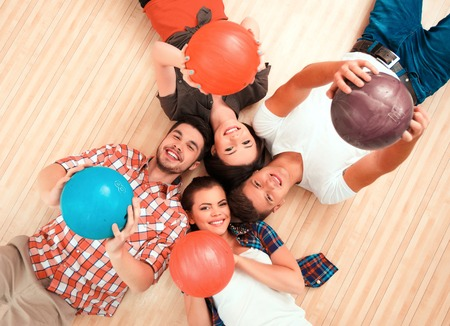 outstretching:  Top view of cheerful friends lying down and outstretching their bowling balls
