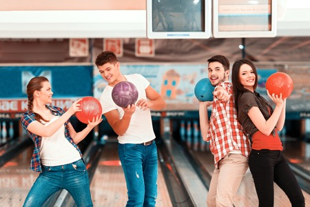 bowling alley: Beautiful young people holding bowling balls and posing against bowling alleys Stock Photo