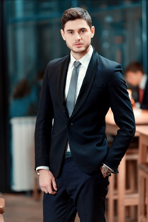 charisma: Confidence and charisma. Cheerful young businessman in full suit looking at camera while standing in the bar during business lunch