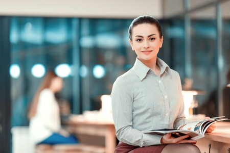hotel worker: Successful business lady. Beautiful young woman in formalwear holding a corporate magazine and smiling while leaning at bar counter Stock Photo