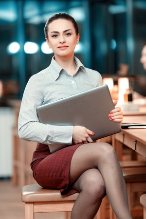 Confident and successful businesswoman. Portrait of beautiful young woman in formalwear smiling at camera while sitting at the bar and holding laptop