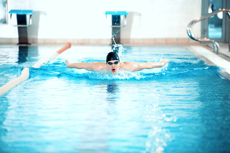 front raise: Refreshing exercise. Young dynamic swimmer performing the butterfly stroke in the pool Stock Photo