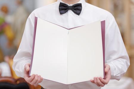 meseros: Camarero Alegre. Imagen recortada de camarero joven y guapo en camisa y pajarita sosteniendo un menú con las páginas en blanco para el espacio de copia en el restaurante de lujo