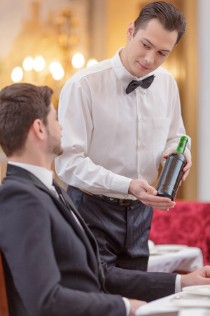 Choosing wine. Sommelier proposing wine to handsome man in suit sitting at the restaurant photo