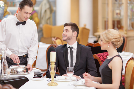 romantic evening with wine: Couple in restaurant. Confident waiter serving the table with salad while beautiful couple looking at him and smiling while sitting in luxury restaurant with selective focus Stock Photo