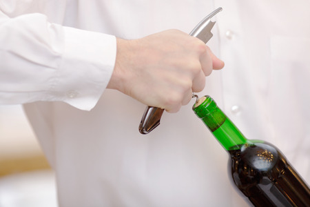 cork screw: Serving wine. Closeup image of waiter opening a bottle of red wine with a cork screw Stock Photo