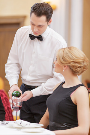 waiter: It is our best wine. Handsome waiter serving wine to his beautiful female client while sitting in the luxury restaurant Stock Photo