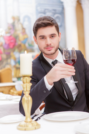 Making a toast. Handsome young man in suit raising his glass of wine while making a toast in luxury restaurant photo