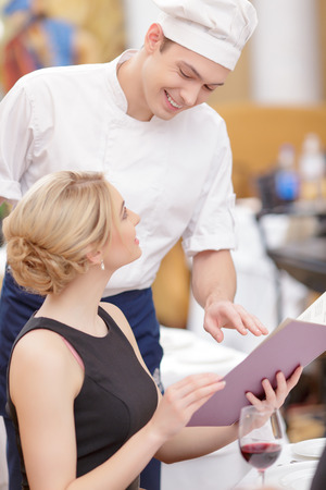 Specials from the chief. Confident chef giving his recommendations to beautiful woman looking at menu while sitting in luxury restaurant photo