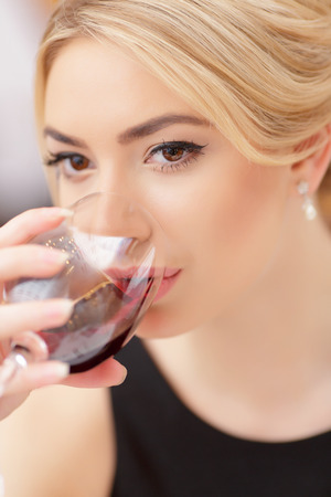 Making a toast. Closeup of beautiful young woman in dress drinking wine while having dinner in luxury restaurant photo