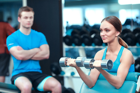 under control: Weight exercise. Beautiful young woman in sports clothing exercising with dumbbells while sitting on the bench of gym under control of her sports instructor Stock Photo