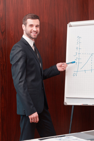great suit: Great presentation. Handsome man in suit and necktie standing near whiteboard and pointing it with smile