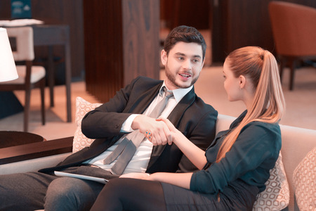 Good deal. Two people in formalwear handshaking and looking at camera while sitting on the couch during business meeting Stock Photo