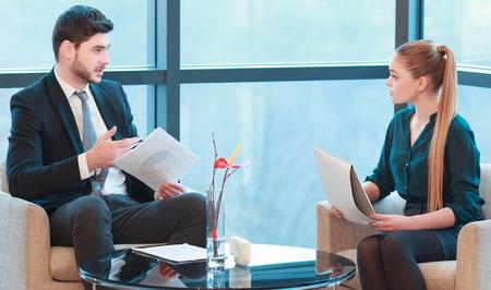 patron: Encuentro con un jefe. Imagen de la hermosa mujer joven y el hombre en ropa formal con reuni�n de negocios mientras est� sentado contra la ventana de la oficina Foto de archivo
