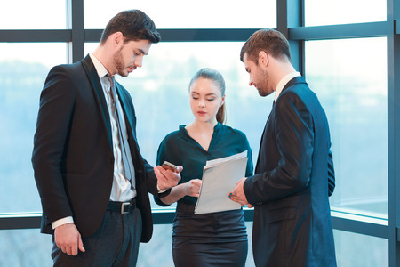Checking schedule with colleagues. Group of business people in formal wear looking at the screen of mobile phone while standing against the window in the meeting room Stock Photo