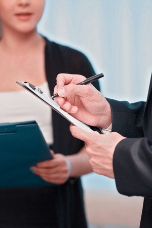 reporting: Assistant at work. Closeup of beautiful young woman in formalwear holding documents and reporting while having meeting with her boss Stock Photo