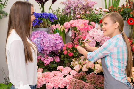 freshest: Only the freshest flowers. Young smiling florist showing flowers to the customer at the flower store
