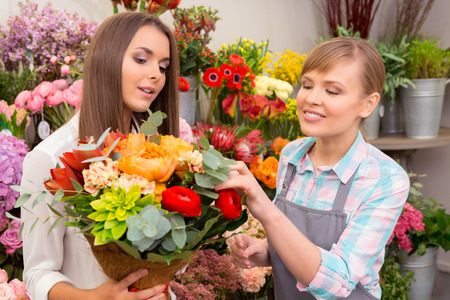 flower shop: Cannot stop wondering its beauty. Young cheerful florist showing to customer flowers in bouquet