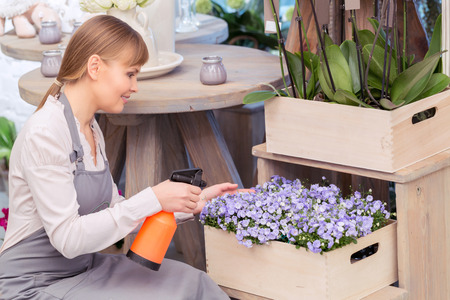 freshest: Only the freshest flowers. Young florist spraying water onto a floral arrangement at the wooden flower stand