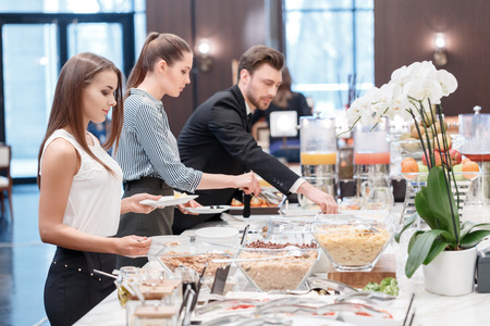sweet table: Everything is so fresh and tasty. Two businesswomen and a businessman standing by the catering table and taking dishes for the business lunch