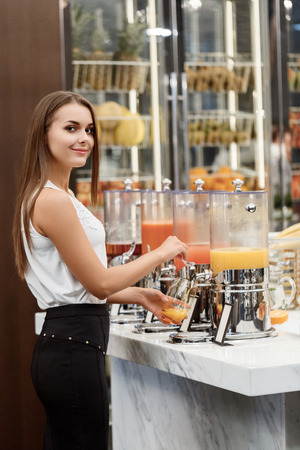 keep fit: Fruit juice is a right thing to keep fit. Young beautiful woman in official attire taking juice at buffet restaurant