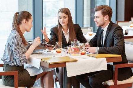 negocios comida: Totalmente en desacuerdo. Los gerentes de negocios tienen una discusión activa de los datos de la empresa durante el almuerzo en el restaurante
