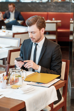 answer phone: Need to answer. Vertical view on the young attractive business manager looking at his phone during business lunch with colleagues Stock Photo