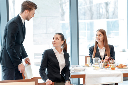 anticipated: Such an anticipated meeting. Young businessman assists his female business partner to sit comfortably by lunch table Stock Photo