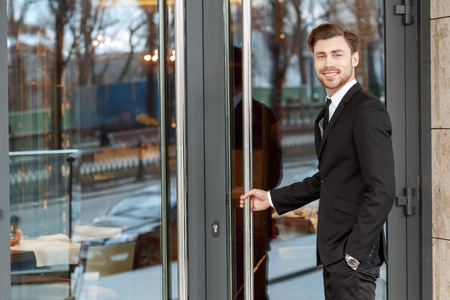 enters: Ready to come in. Young handsome smiling businessman enters the business center