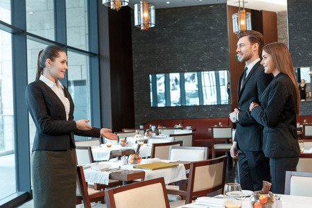suggests: Feeling at ease at the meeting. Female business manager suggests place for lunch to her business partners in the restaurant Stock Photo